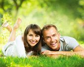Happy Smiling Couple Outdoors. Relaxing on Green Grass. Park. Young Family Lying on Grass Outdoor. N