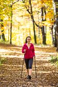 Nordic walking - active woman exercising outdoor
