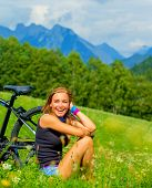 Cheerful female resting on green field after riding on bicycle, Alps mountains background, biking traveling along Austria, summer vacation concept
