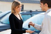 picture of car key  - cropped view of man in car dealership giving car keys to client - JPG