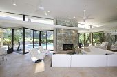 Sunken seating area and exposed stone fireplace in spacious living room with view of swimming pool a