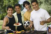 pic of tong  - Portrait of happy male friends barbecuing food at park - JPG
