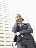 Low angle view of businesswoman conversing mobile phone against tall office building