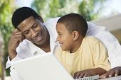 Happy father and son using laptop together