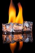 stock photo of unnatural  - Ice cubes melting with flame on shiny black surface - JPG