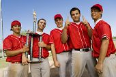 Portrait of successful baseball team with trophy on field