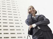 Low angle view of businesswoman using mobile phone against tall office building