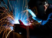 Welder Shielding Sparks From Metal