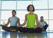 Multiethnic people sitting in lotus position at gym