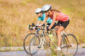 Two Women Exercising On Bicycles  Outdoors. Horizontal Image