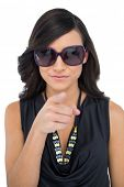 Elegant brunette wearing sunglasses pointing at camera on white background
