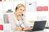 Portrait of smiling young woman operator in headset at office.