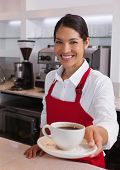 Pretty young barista offering cup of coffee smiling at camera in a cafe