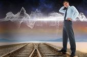 Thinking businessman with hand on head against train tracks under energy wave in desert