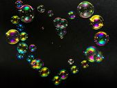 Multicolored Bubbles In The Form Of Hearts On A Dark Background