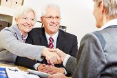 Happy elderly couple shaking hands with legal consultant in law firm