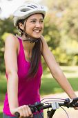 Portrait of a fit young woman with helmet riding bicycle at the park