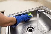 Woman Scrubbing Sink With Scrubber