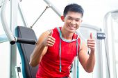 Asian Chinese man having fitness training or workout in gym doing sport to build up muscle on a weig