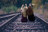 Two Girls Sitting On Railway Tracks And Show Love