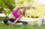 Full length of a healthy and beautiful young woman doing stretching exercise in the park