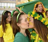 Cheerful couple of Brazilian girlfriends soccer fans kissing each other celebrating victory.
