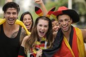 Happy group of German sport soccer fans celebrating victory together.