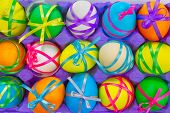 Colorful easter eggs in tray on white background