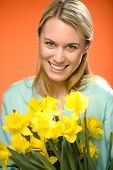 Smiling woman holding yellow narcissus spring flowers on orange background