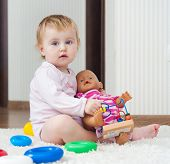 stock photo of baby doll  - cute baby playing with doll at home - JPG