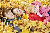 Mother and her two children lie in autumn park in drift of fallen leaves and look at the sky
