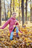 Little girl runs along autumn park kicking up fallen leaves with her boots and jumps