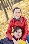 Woman sits on fallen leaves in autumn park and man head lies on her knees