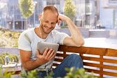 Happy man reading e-book outdoors, smiling, using earbuds.
