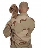 Marine in camouflage uniform with a dog standing on a white background