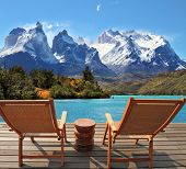 The magnificent national park Torres del Paine in Chile. Lake Pehoe. Two wooden chairs mounted on a wooden platform.  The comfortable place to enjoy the beauty of the landscape.
