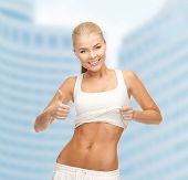 fitness and diet concept - beautiful sporty woman showing thumbs up and her abs