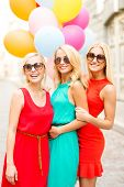 holidays and tourism, friends, hen party, blonde girls concept - three beautiful women with colorful balloons in the city