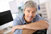 Smiiling mature man relaxing in office chair