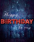 Grunge background with glowing letters writing Happy Birthday to you