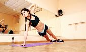 Young fit woman doing fitness exercises at gym