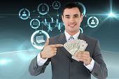 Businessman pointing at bank notes in his hand against online community background