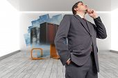 Thoughtful businessman with hand on chin against abstract screen in room showing server towers