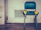 stock photo of discard  - A Grungy Retro Damaged Chair Outside A Workplace - JPG