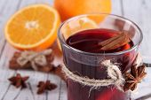 Mulled wine with oranges and spices on table close up