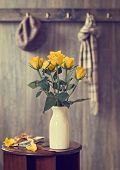 Display of yellow roses on hallway table with letters tied with ribbon