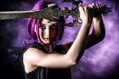 stock photo of sword  - Beautiful girl warrior with a sword standing in fighting stance - JPG
