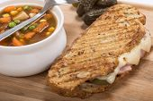 Delicious panini made with ham, pork and swiss cheese served with a vegetable soup, sweet potato fri