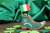 Saint Patrick day boot with gold coins and clover leaves on green satin background