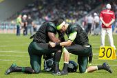 VIENNA,  AUSTRIA - APRIL 21 QB Jonathan Dally (#8 Dragons) and RB Tunde Ogun (#1 Dragons) pray befor